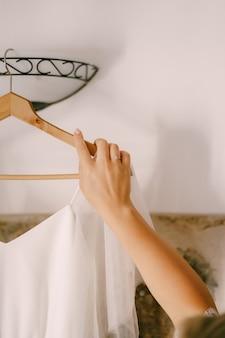 Рука невесты, держащая вешалку с свадебным платьем