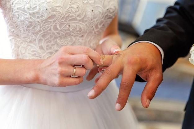 Bride hand putting wedding ring on groom finger