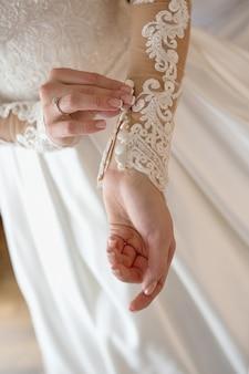 彼女のウェディングドレスのボタンを閉じる花嫁の手