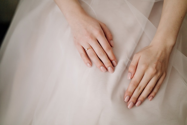 Bride hands with manicure on her dress