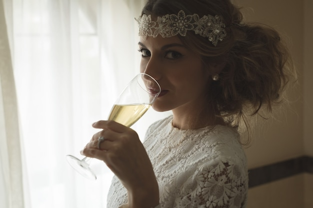 Bride having a glass of champagne at home