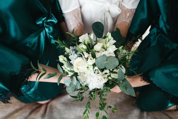 The bride and her friends hold a wedding bouquet