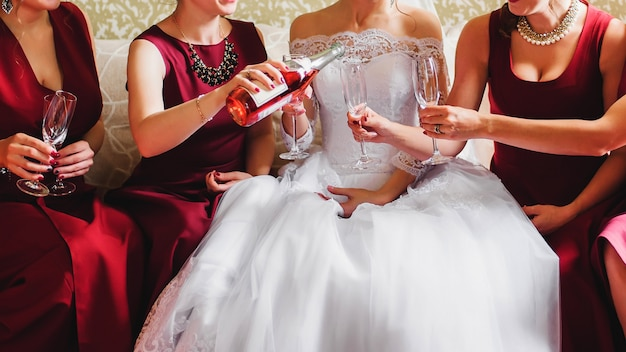Bride and her friends in red dresses at wedding pour champagne on glasses