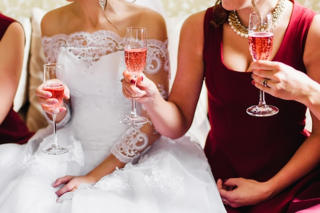 Bride and her friends at the wedding celebrate with glasses of champagne in the hands