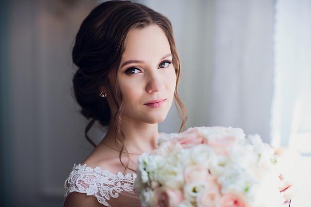 Невеста проведет свадебный букет из розовых пионов и роз.