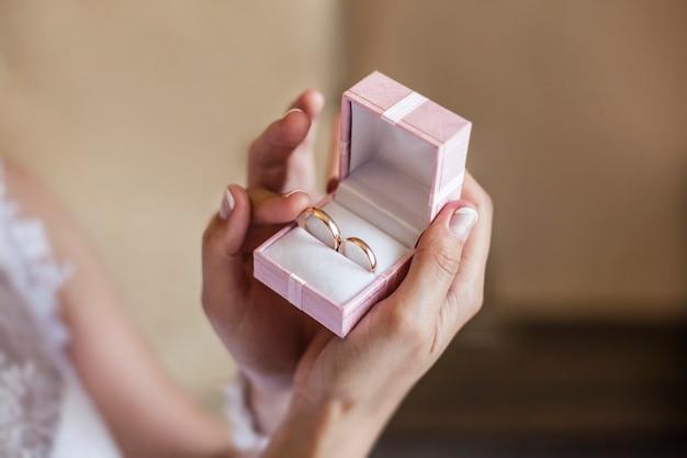 Невеста держит коробку с обручальными кольцами в день свадьбы крупным планом