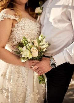 Невеста держит свадебный букет в руках, стоя возле жениха