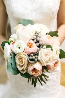 花嫁の結婚式のブーケを持って