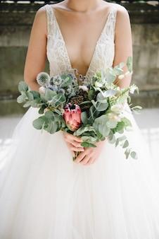 Невеста держит красивый цветочный букет в день своей свадьбы