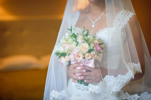 Bride holding beautiful wedding bouquet in bedroom
