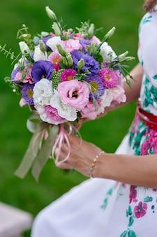 Bride holding beautiful wedding bouquet close up