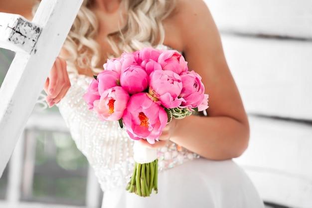 ピンクの牡丹の美しいウェディングブーケを保持している花嫁