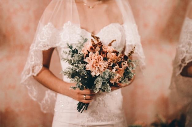 Sposa con in mano il bellissimo bouquet da sposa