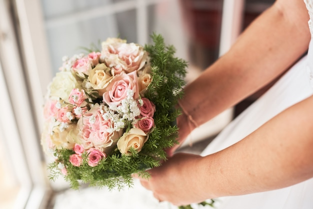 Bride holding a bouquet of pink roses in a rustic style.