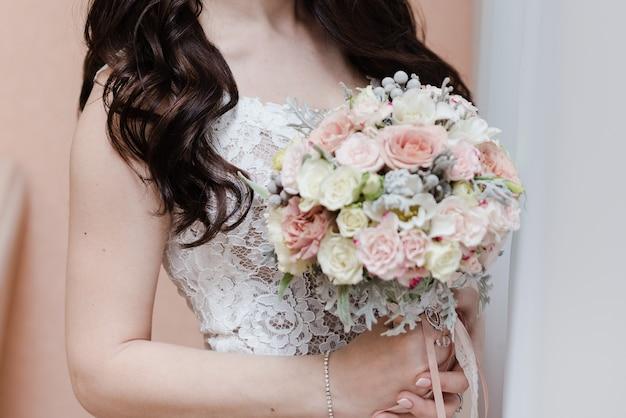 花束を保持している花嫁結婚式の日のブライダルブーケ