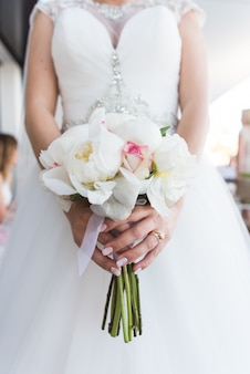 Bride holding a bouquet of white peonies and roses.