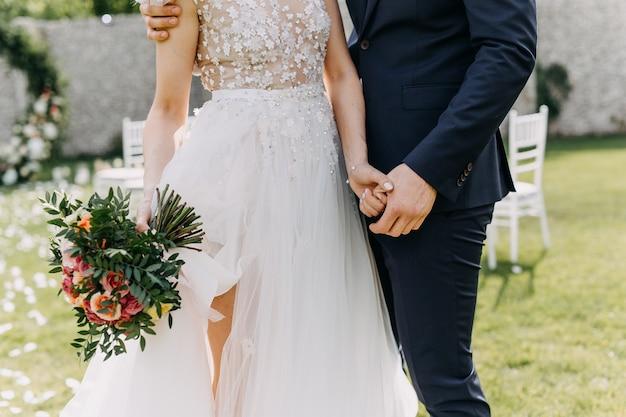ブライダルブーケを持って、新郎の手を握って花嫁