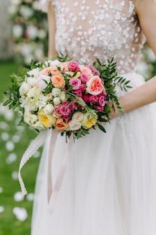 さまざまな花で作られたブライダルブーケを保持している花嫁