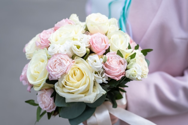 屋外でバラのブライダルブーケを保持している花嫁。