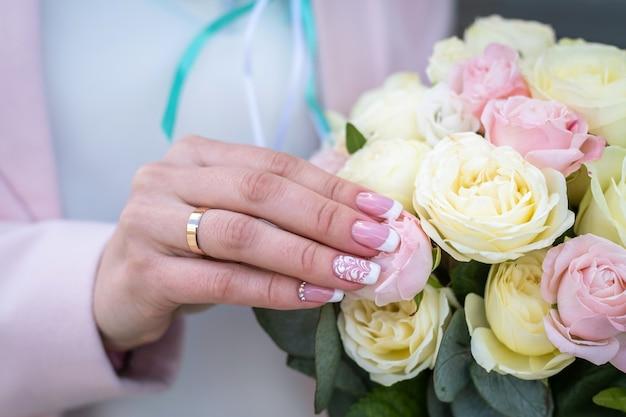 バラのブライダルブーケを保持している花嫁。指に結婚指輪。
