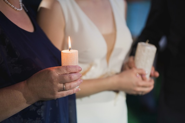 Bride holding a candle in her hands