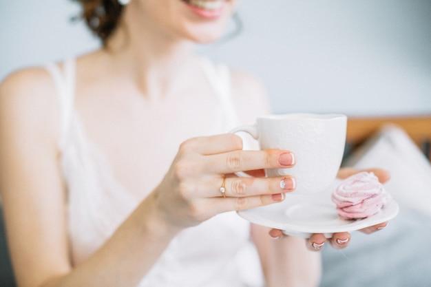 Невеста держит чашку кофе и печенья.