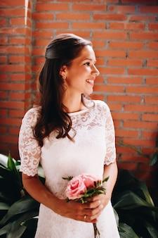 ピンクのバラの小さなウェディングブーケを持って花嫁。結婚式の日のコンセプトです。