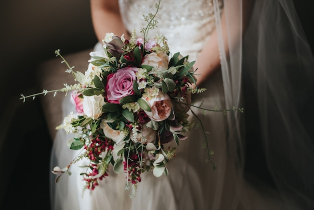 美しいバラの彼女の結婚式の日の花束を保持している花嫁