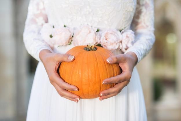 Bride holding pumpkin in her hands