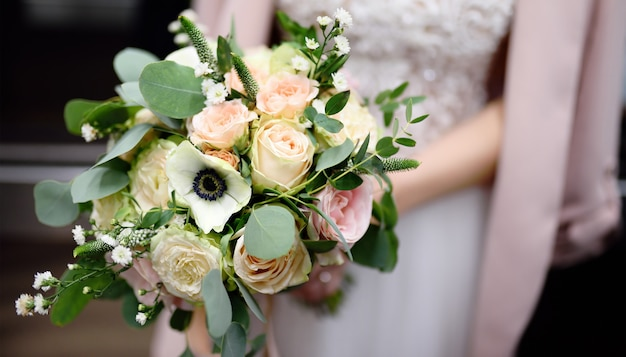 Bride holding stylish wedding flowers bouquet
