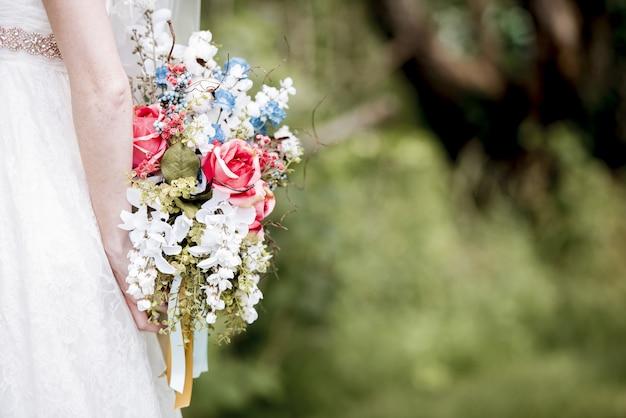Невеста держит за спиной букет цветов