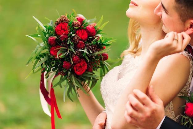 Bride holding wedding bouquet beautiful red peonies hugging