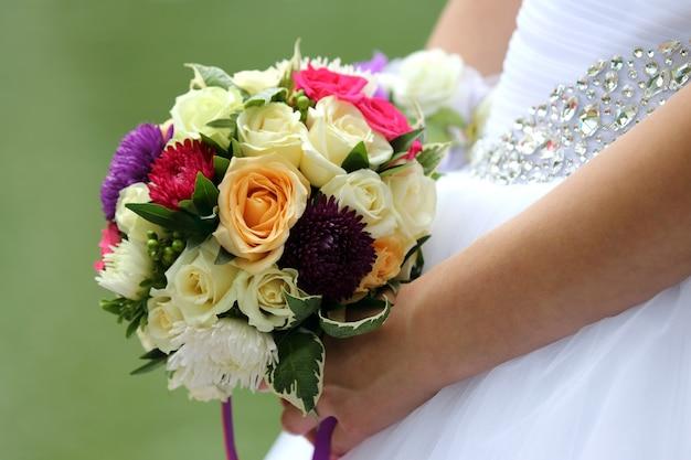 結婚式の花束のクローズアップを保持している花嫁
