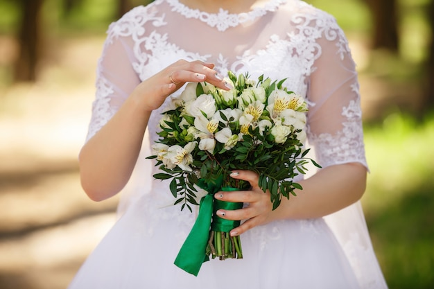 Bride holding wedding bouquet of fresh flowers, green wedding