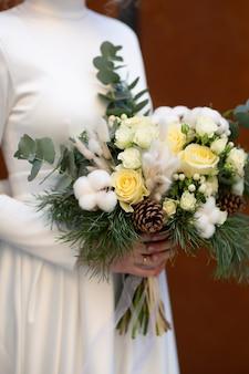 松、ユーカリ、綿、白いバラ、ラグラスのウェディングブーケを保持している花嫁