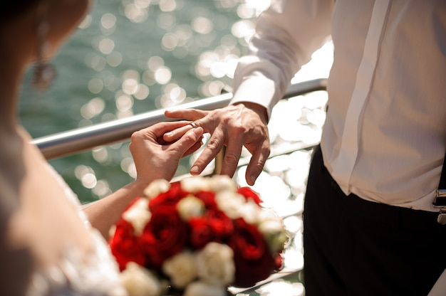 Bride holding a wedding bouquet and putting on a wedding ring to a broom in the background of the sea