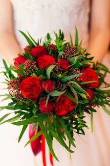 Bride holding wedding bouquet of red peonies and green leaves close up