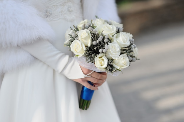 Bride holding wedding bouquet of white roses.