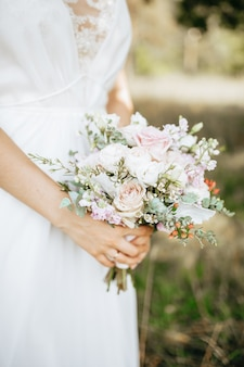 Bride holding wedding bouquet with white and pink flowers