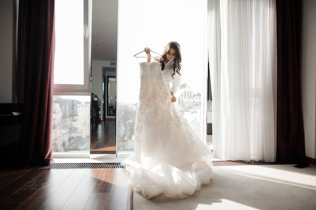 Bride holding wedding dress on a hanger near window