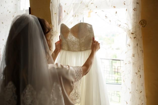 Bride holding wedding dress