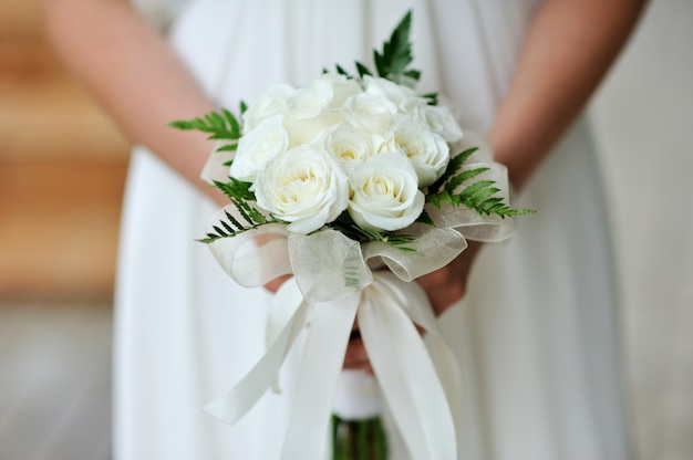 Bride holding wedding flower bouquet of white roses