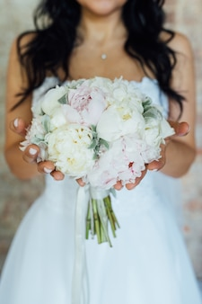 Bride holding white wedding bouquet of roses and love flower.