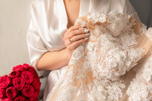 Bride holding white wedding dress with lace, embroidery.