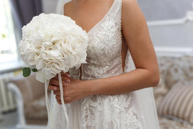 Невеста держит красивый свадебный букет из белых цветов крупным планом. молодая девушка в белом платье с нежным букетом. стильный свадебный букет из белых цветов в помещении. день свадьбы. детали свадьбы