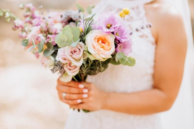 Невеста держит свадебный букет. нежный букет с жёлтыми розами и эвкалиптом.