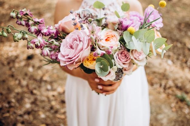 花嫁はウェディングブーケを保持しています。黄色いバラとユーカリの繊細な花束。