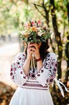 신부는 가을 공원에서 수 놓은 드레스에 그녀의 손에 꽃의 웨딩 부케를 보유하고 있습니다.