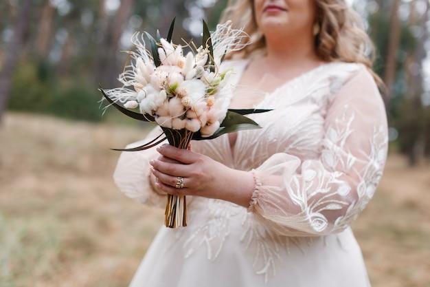 花嫁は屋外で白とベージュの花の結婚式の花束を保持しますl女性の手でお祝いの花束