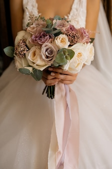 Bride holds beautiful bouquet with roses and eucalyptus
